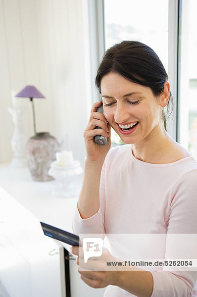 Frau Homeshopping am Telefon mit Kreditkarte
