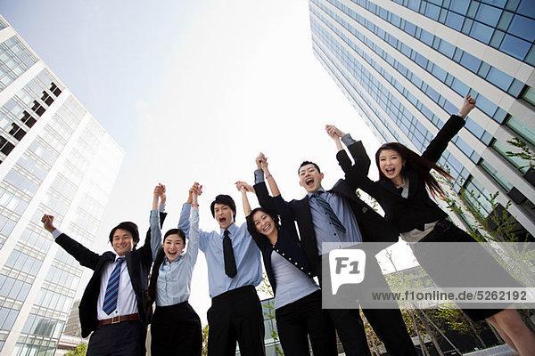 Geschäftsleute in einer Reihe  die Arme in der Luft