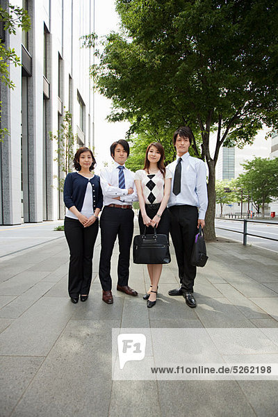 Four businesspeople on sidewalk