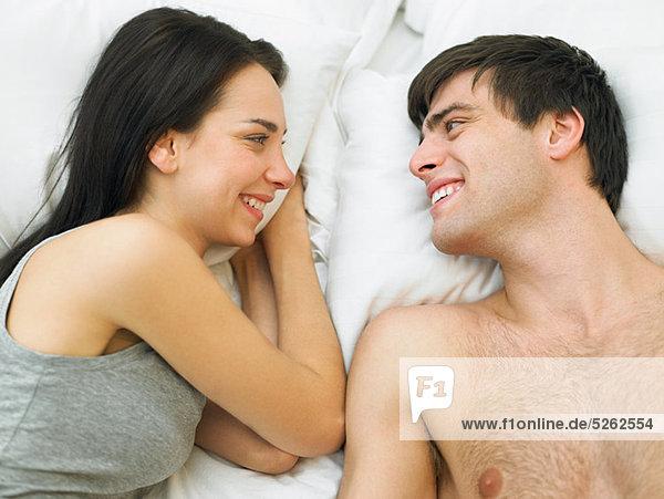 Junges Paar liegt im Bett