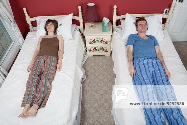 Junges Paar auf Einzelbetten liegend  sich gegenseitig ignorierend