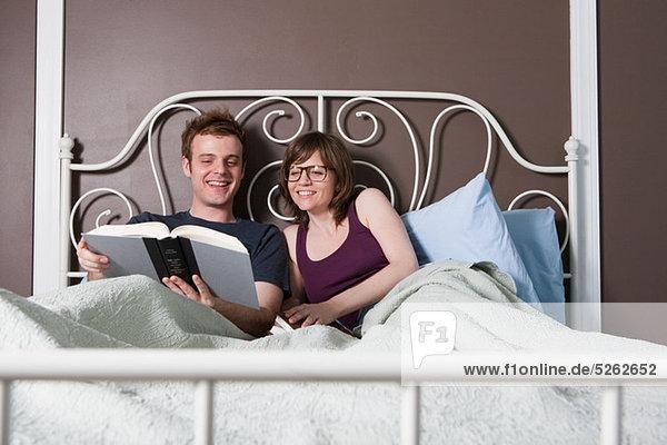 Young couple lesen im Bett