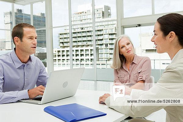Drei Geschäftsleute treffen sich im Büro mit Laptop