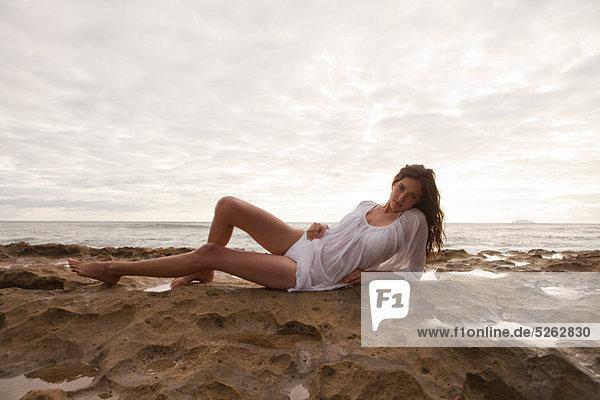Young Woman wearing weiß oben sitzen auf Sand,  Porträt