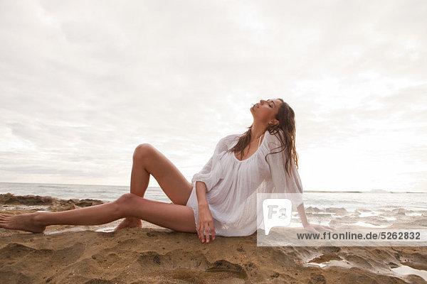 Young Woman wearing weiß oben sitzen auf Sand  Porträt