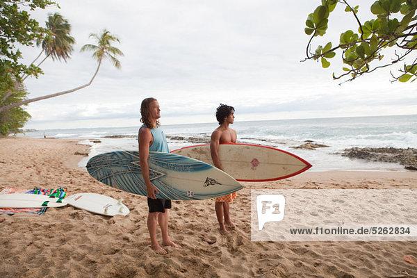 Zwei Männer halten Surfbretter am Strand