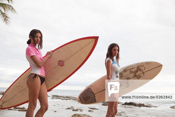 Zwei junge Frauen  die halten Surfbretter  Porträt