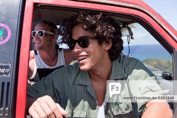 Zwei Männer  die im Urlaub aus dem geöffneten Autofenster schauen.