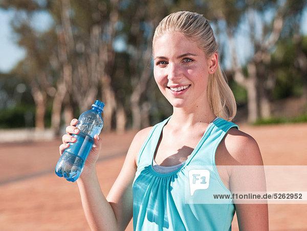 Young Woman holding Flasche Mineralwasser