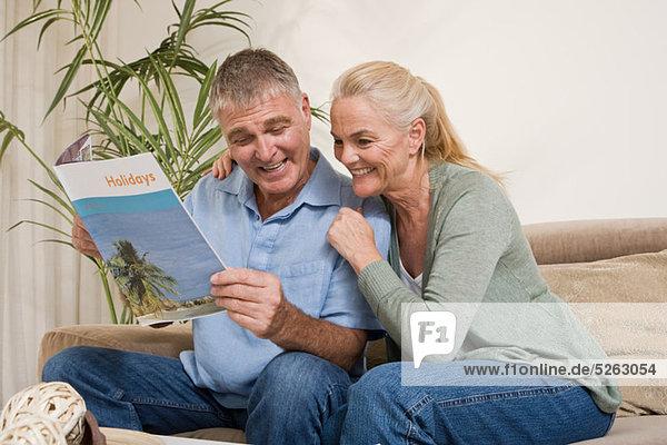Reife Paare mit Urlaubsbroschüre