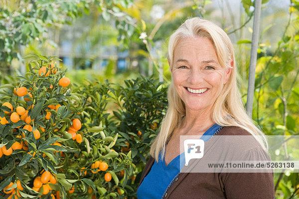 Reife Frau von Obstbaum