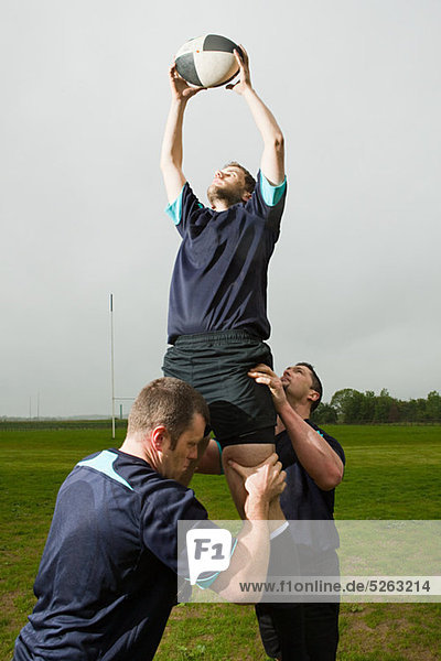 Rugby-Spieler springen zu Ball im Ausgang  unterstützt von Teamkollegen zu fangen