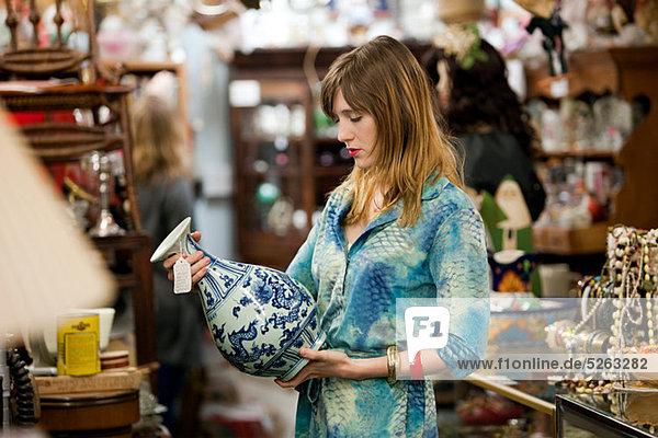 Frau inspiziert Vase im Antiquitätenladen