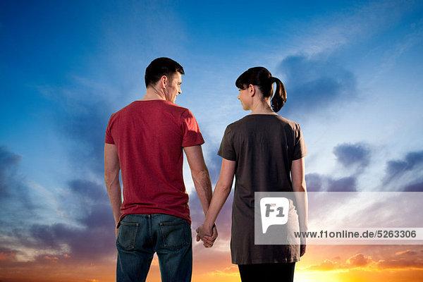 Paar Hand in Hand gegen dramatische Sonnenuntergang  hinten anzeigen
