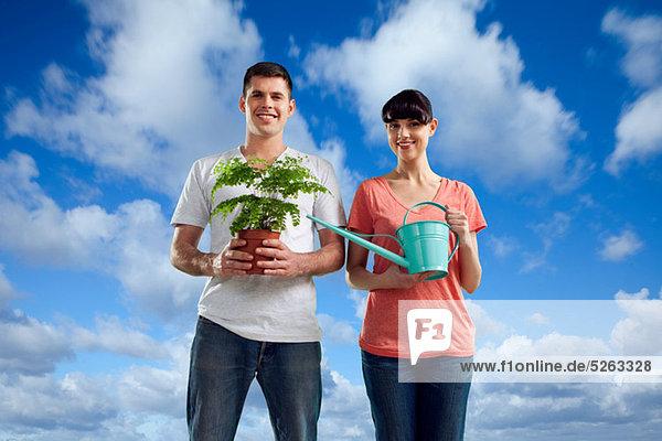 Paar im Bereich mit einer Gießkanne und Pflanze