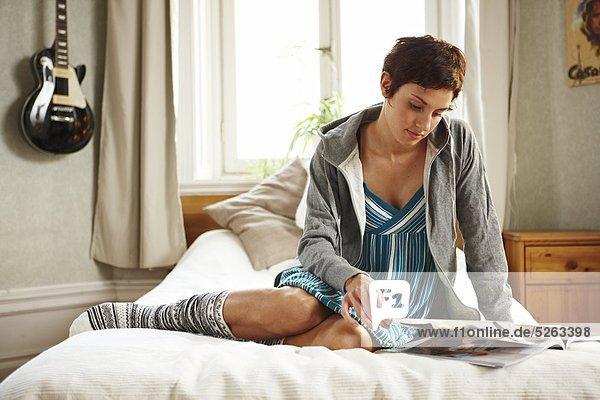 Woman sitting on bed reading magazine