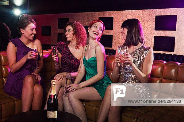 Vier junge Frauen genießen Champagner im Nachtclub
