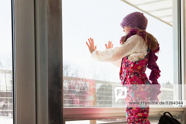 Mädchen schaut durchs Fenster