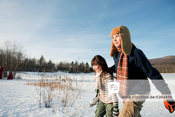 Brother and sister walking in snow