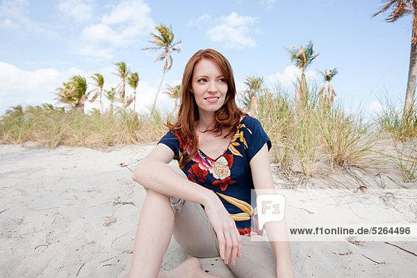 Junge Frau sitzend am Strand  Portrait