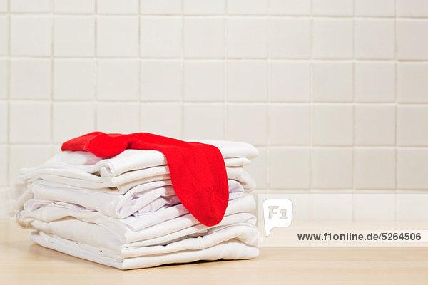 Haufenweise saubere weiße Wäsche und rote Socken