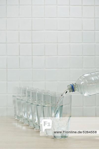 Gießen von Gläsern mit Mineralwasser