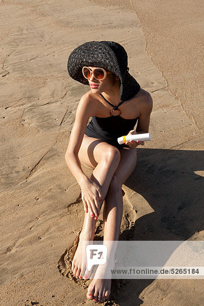 Frau am Strand mit Sonnencreme