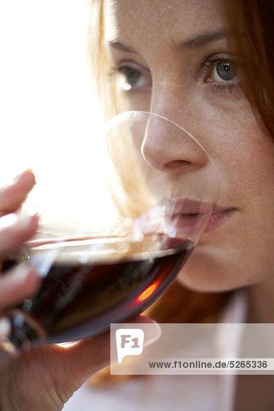 Close up of Mädchen mit rotem Haar trinken Rotwein