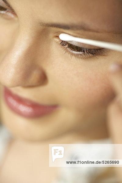 Extreme Nahaufnahme des Mädchens mit einem Wattestäbchen  um die Augen mund