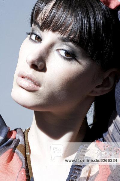 Brünette mit Farbflächen- und rauchigen Augen Make-up tragen gemustert oben