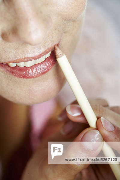 Close-up of mature Woman applying Lip liner mund