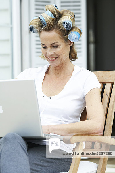 Mature woman with big rollers in her hair on her laptop