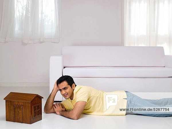 Man lying on floor looking at model of house MR779K