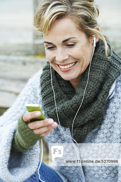 Mature Woman listening to iPod außerhalb