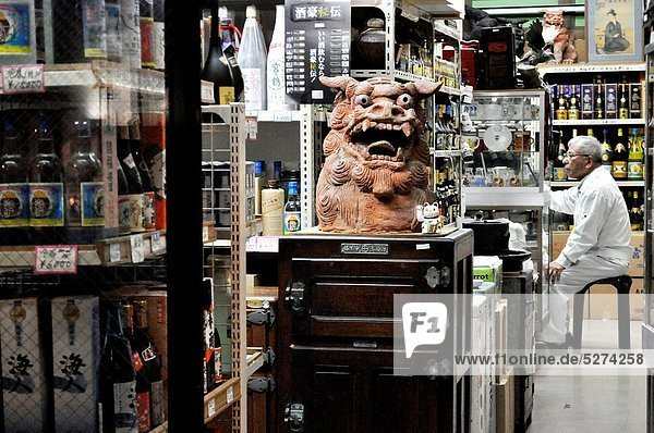 Naha (Japan): liquor store with a shisa statue in the Miebashi neighborhood; Shisa is a traditional Ryukyuan decoration  often in pairs  resembling a cross between a lion and a dog  from Okinawan mythology