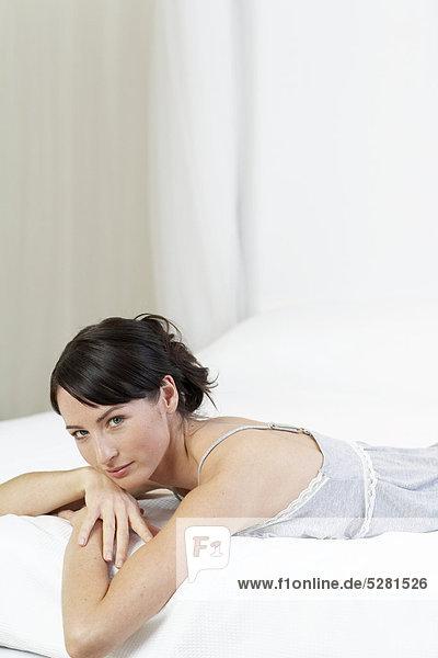 Anschnitt liegend liegen liegt liegendes liegender liegende daliegen Frau Bett Menschlicher Bauch Menschliche Bäuche schießen grau