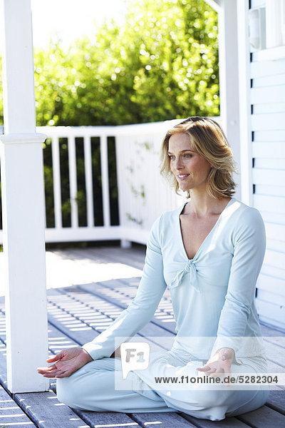 Schöne Frau Yoga auf das Strandhaus durchführen.
