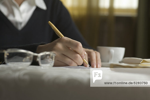 detail of businesswoman signing document during business lunch