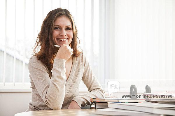 Porträt der jungen Bsinesswoman sitting at desk