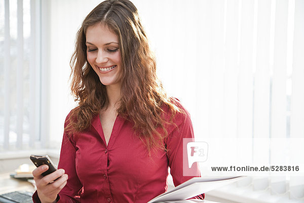 Porträt der jungen geschäftsfrau mit Mobiltelefon