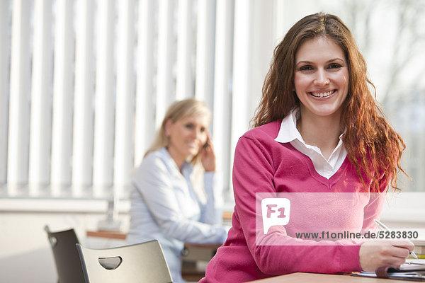 Portrait of young Businesswoman am Schreibtisch sitzen