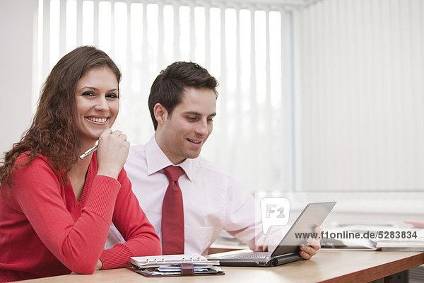 Portrait of young Businesswoman und männlichen Kollegen sitting at desk