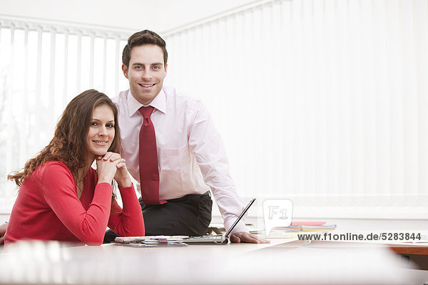 Portrait of young Businesswoman und männlichen Kollegen sitting at desk