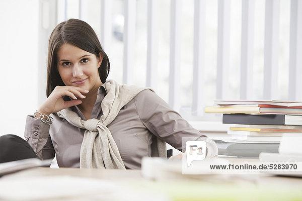 Porträt der jungen Busineswoman an Schreibtisch