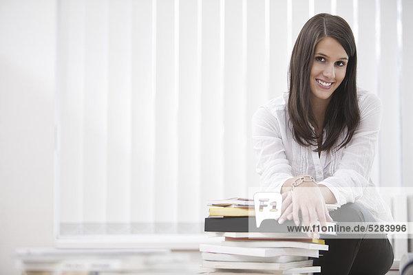 Porträt der jungen geschäftsfrau auf Schreibtisch sitzend