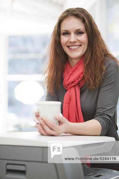 Portrait of young Businesswoman am Kopierer