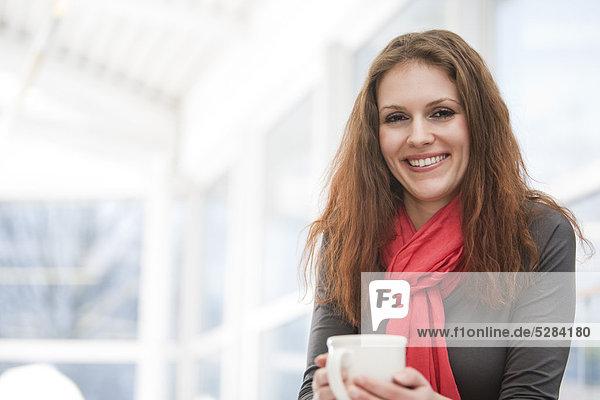 Porträt der jungen geschäftsfrau hält cup