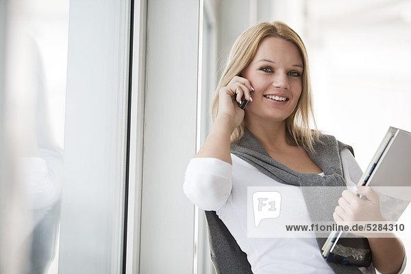 Portrait of young Businesswoman with Dokumente und Handy