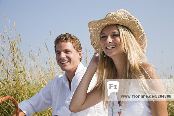 Portrait of young Couple having Picnic auf Wiese