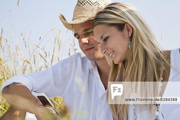 Portrait of young Couple in Wiese lesen SMS-Nachricht auf Handy